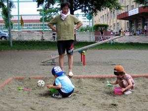 砂場で遊ぶ2人を見守るばーちゃん