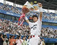 プロ野球32人目の通算2000本安打を達成し、花束を手にファンの声援に応える古田。プロ16年、通算1884試合目で大台に到達。
