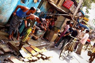 コルカタの水汲み場の写真。ブタの皮で設えた袋に水をためる